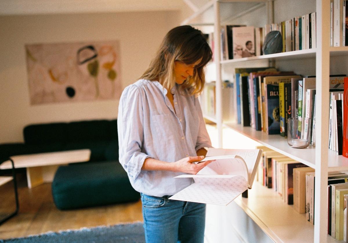 Victoire dans son salon, feuilletant un livre