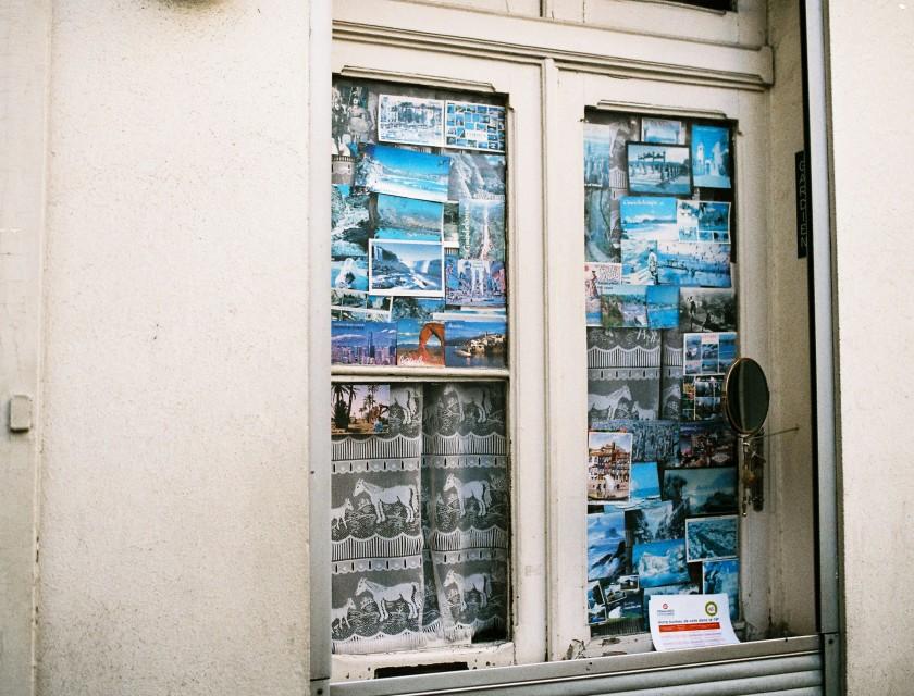Fenêtre recouverte de cartes postales / Paris